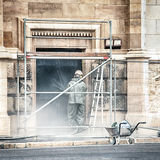 A worker cleaning the facade of a building. A worker restoring the facade of an old stone building with a pressurized water gun Stock Image