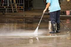 Worker cleaning floor with air high pressure machine background Stock Photos