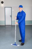 Worker cleaning floor. Happy Mature Male Worker Cleaning Floor With Mop Stock Images