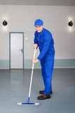 Worker Cleaning Floor. Happy Mature Male Worker Cleaning Floor With Mop Royalty Free Stock Images