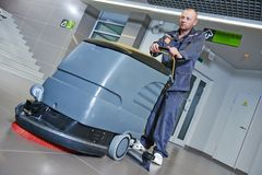 Worker cleaning floor with machine Royalty Free Stock Photos