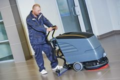Worker cleaning floor with machine Royalty Free Stock Image