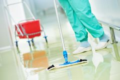 Worker cleaning floor with machine. Floor care and cleaning services with washing mop in sterile factory or clean hospital Royalty Free Stock Photo