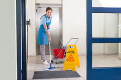 Worker Cleaning Floor With Mop. Happy Female Worker In Uniform Cleaning Floor With Mop Royalty Free Stock Photo