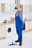 Worker Cleaning Floor With Mop. Young Male Worker Cleaning Floor With Mop In House Royalty Free Stock Photography