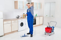 Worker Cleaning Floor With Mop. Young Male Worker Cleaning Floor With Mop In House Royalty Free Stock Photos