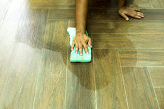 Worker cleaning floor tile after grouting tiles with sponge Royalty Free Stock Photography