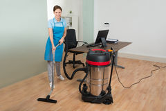 Worker Cleaning Floor With Vacuum Cleaner Royalty Free Stock Image