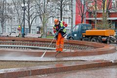 Worker cleaning a fountain with pressure washer in Novopushkinsky square in Moscow stock photography