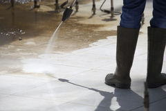 Worker Cleaning a Fountain by Pressure Washer Royalty Free Stock Images