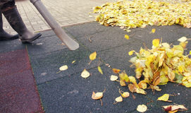 Worker cleaning ground in the autumn park from yellow leaves Royalty Free Stock Photo