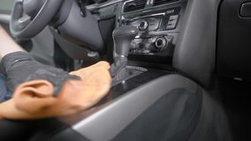 Worker is cleaning handle of gearbox and control panel inside automobile in a car washing service. Close-up of hands stock video footage