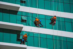 Worker cleaning high tower in big city Stock Images