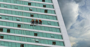 Worker cleaning high tower in big city Royalty Free Stock Image