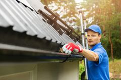 Worker cleaning house gutter stock photography
