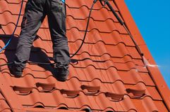 Worker cleaning metal roof with high pressure water stock photography