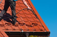 Worker cleaning metal roof with high pressure water Stock Image