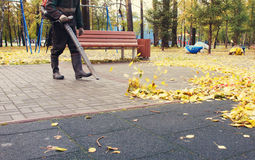 Worker cleaning playground in the autumn park from dead leaves. With a blower Royalty Free Stock Image