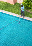 Worker cleaning the pool. Stock Photography