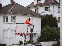 Worker cleaning repairing changing the light tube of a light mas. PARIS, FRANCE - DEC 16, 2017:  Worker cleaning repairing changing the light tube of a light Royalty Free Stock Photography