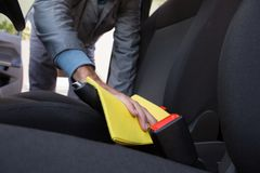 Worker cleaning seat inside the car. Male worker cleaning seat inside the car Stock Images