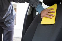 Worker cleaning seat inside the car. Male worker cleaning seat inside the car Stock Image