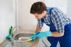 Worker Cleaning Sink In Kitchen Room. Young Worker Wearing Glove Cleaning Steel Sink In Kitchen Room Royalty Free Stock Photos