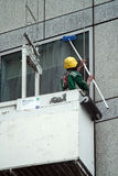 Worker cleaning skyscraper mirrored windows Royalty Free Stock Photography