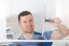 Worker Cleaning Soap Sud On Window With Squeegee Royalty Free Stock Photos