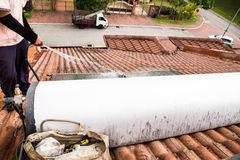 Worker cleaning solar water heater on roof during maintenance Royalty Free Stock Photography