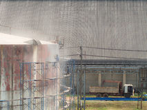 Worker cleaning storage tank by air pressure sand blasting Stock Photo