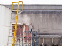 Worker cleaning storage tank by air pressure sand blasting Royalty Free Stock Photo
