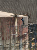 Worker cleaning storage tank by air pressure sand blasting Stock Photography
