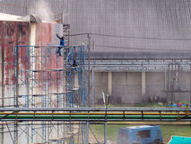 Worker cleaning storage tank by air pressure sand blasting. Royalty Free Stock Photos