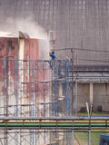 Worker cleaning storage tank by air pressure sand blasting. Stock Images