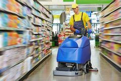 Worker cleaning store floor with machine. Floor care and cleaning services with washing machine in supermarket shop store