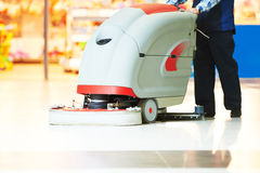 Worker cleaning store floor with machine Stock Photography