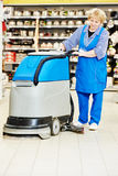 Worker cleaning store floor with machine Royalty Free Stock Photos
