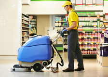 Worker cleaning store floor with machine Stock Photos