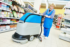 Worker cleaning store floor with machine Royalty Free Stock Image