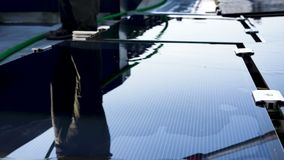 Worker is cleaning up solar panels. Someone is cleaning solar panes with mop stock footage