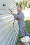 Worker cleaning wall corrugated iron. Worker cleaning a wall of corrugated iron Royalty Free Stock Photo
