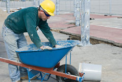 Worker Cleaning Wheel Barrow. Construction worker cleaning mortar from wheel barrow stock photo