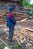 Worker cleans the area of forestry production royalty free stock image
