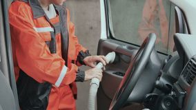 Worker cleans the cabin of car with vacuum cleaner. Car washman cleans the interior of automobile. Worker uses vacuum cleaner to clean the cabin of car from stock video