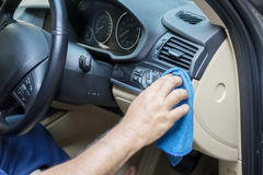 Worker cleans the car dashboard with cloth Stock Photos