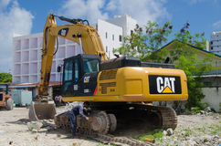 Worker cleans excavator at construction site Stock Images