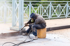 Worker cleans the metal structures sandblasting tool Royalty Free Stock Image