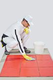 Worker cleans red tiles Stock Images