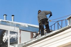Worker cleans the roof of the house from snow royalty free stock images